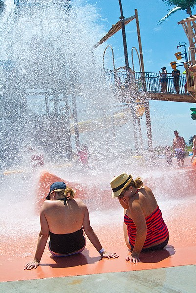 Women get wet with a giant spray of water that goes off every 3 minutes at Andy Alligator's water park recently.