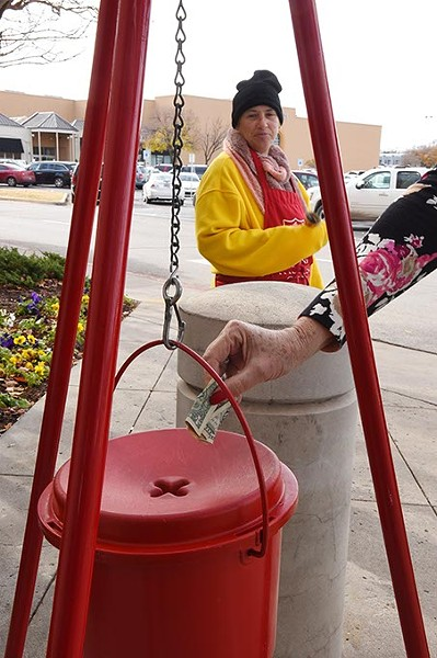A woman donates a few dollars at the Salvation Army collection kettle, manned by Gladys Brady, a paid bell ringer, near an entrance to Penn Square Mall. - MARK HANCOCK