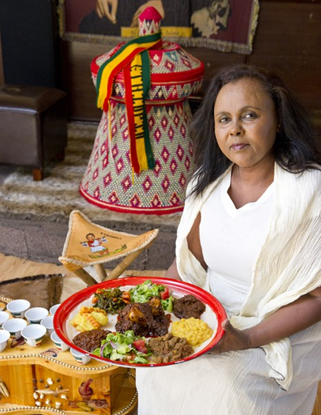 Co-owner Mimi Younis holds the Queen of Sheba Mesob Dish sitting in the traditional Ethiopian dining room-from top left and clockwise potaoes and carrots, green beans and carrots, salad, beef kawatt, chickpea, lamb, salad, lentil. Chicken in the middle. All on top of Qutenga, fried Injera lightly buttered and spiced. Photo/Shannon Cornman - SHANNON CORNMAN