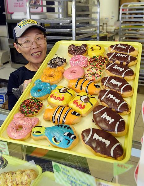 Sarah Lee shows a tray of donuts at Daylight Donuts, Friday, Nov. 18, 2016. - GARETT FISBECK