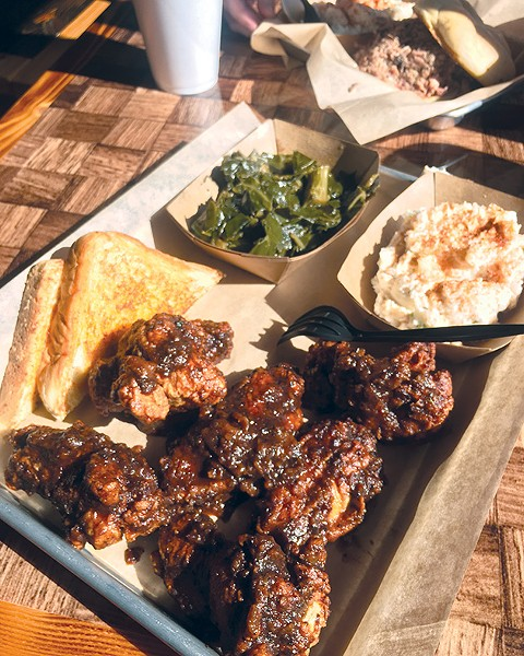 Fried chicken wings covered in jerk sauce with potato salad and greens at Cornish Smokehouse - JACOB THREADGILL