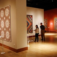 Seth Spillman and Tabbi Burwell look at quilts during the Quilts and Color Media tour, Wednesday, November 4, 2015.