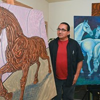 """Artist and teacher, Carlos Tello with work in his living room including, """"Aztec Horse, left, and """"Blue Moon"""", both will be featured during this years Fiestas de las Americas on October 3rd, 9-17-15."""
