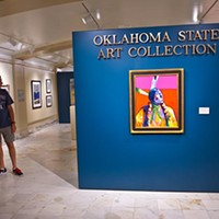 A man and a boy look around near the entrance to the Oklahoma State Art Collection gallery, on the first floor of the State Capitol.  mh