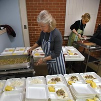 "From left, Barbara Hill and Alison Calhoon, volunteers with Westminster Presbyterian Church in Crown Heights, dole out portions of ""Hoppin Johns"", cornbread, and cherry crisp dessert, for the  Mobile Meals program being delivered shortly after it's ready, to neady recepients on New Years Eve, 12-31-15, in OKC."