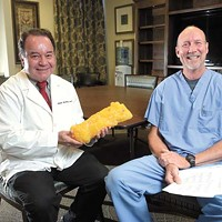 Dr. J. Arden Blough and Chiropractor Todd Farris pose for a photo at Broadway Clinic in Oklahoma City, Monday, Jan. 16, 2016.  Dr. Blough holds a prop representing five pounds of body fat.