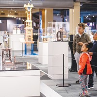 """Guests examine Jim Casey's """"Ezra the Chronicler"""" and """"Henry the Contemplative Robot"""" in Life Imagined: The Art and Science of Automata in Science Museum Oklahoma's smART Space galleries."""
