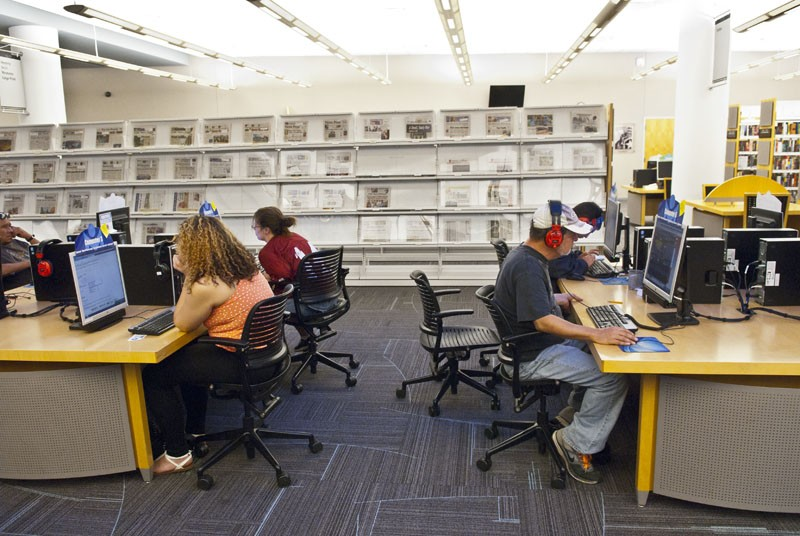 Visitors to the downtown library in Oklahoma City work on computers. - MARK HANCOCK