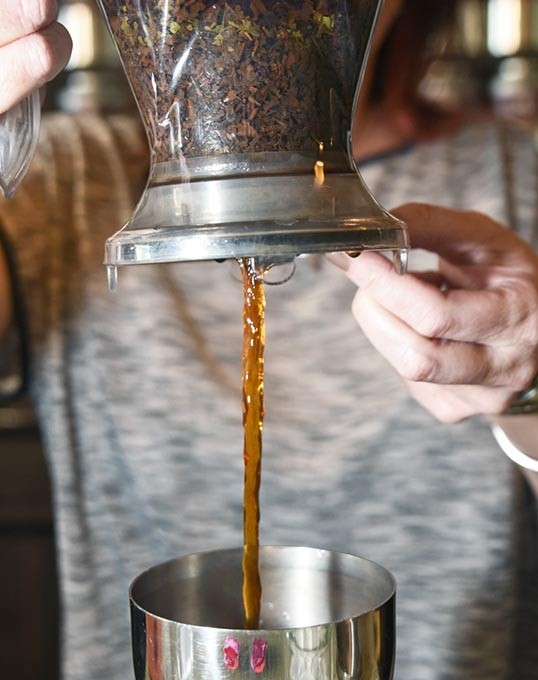 Kristy Jennings, owner of t an Urban Teahouse, pours the hot tea into the first cooling container filled with Ice.  mh