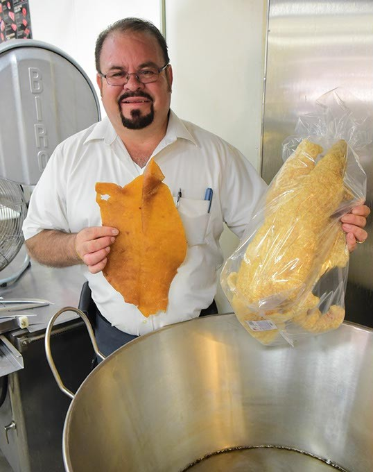 """Marcelino """"Chelino"""" Garcia himself shows the unfried and the finished fried Pork Rinds in a bag over the vat they are fied in, at Chelino's Meat Market, 2101 S. Robinson Avenue, 9-4-15. - MARK HANCOCK"""