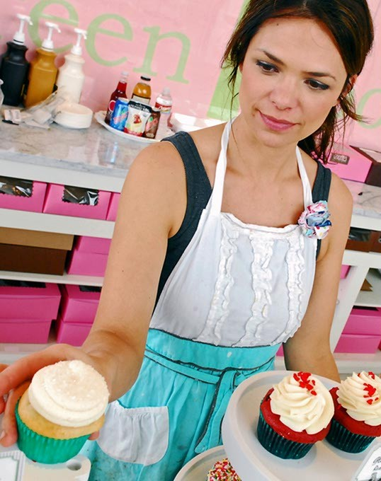 Tiffany Magness, owner of Green Goodies, adjusts her cupcakes at Classen Curve. - MARK HANCOCK