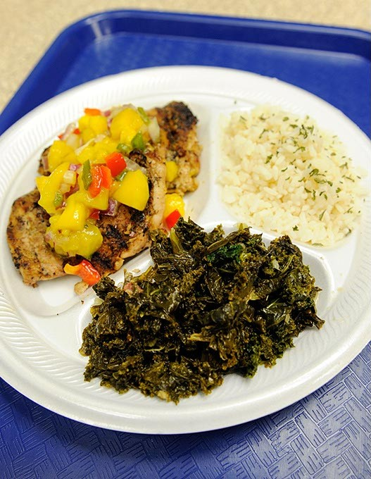 Jerk chicken with mango salsa, island rice (coconut lime infused), callaloo (kale), at The Islands in Oklahoma City, Friday, June 5, 2015.  (Garett FIsbeck