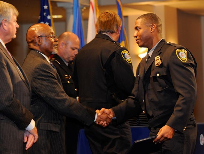 Anthony Anderson, right, graduates during the Oklahoma City Police Academy Recruit Class 132 graduation at First United Methodist Church, Thursday, Dec. 4, 2014. - GARETT FISBECK