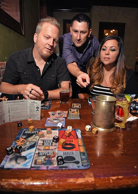 From left, Johnnie Payne, Anthony Vandyousefi, and Layla Payne, check out the roll of dice during a (Moch) game of Firefly over drinks, 10-7-15. - MARK HANCOCK