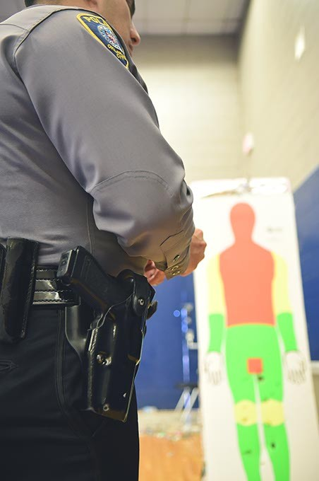 Captain Paco Balderrama's holster and gun with taser target in background, at the OKC Police Training Center.  mh