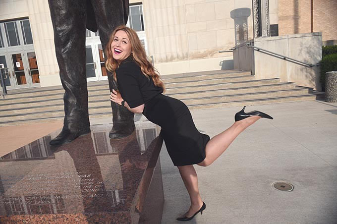 Allison Goodman, a member of Overture young professionals group, plays around at the base of the conductor sculpture in front of the Civic Center Music Hall.  mh