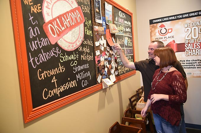 Perk Place Cafe owners Natalie and Jeff Meyer, look over charity donations, Make in Oklahma connections, and biz card bulletin board.  mh