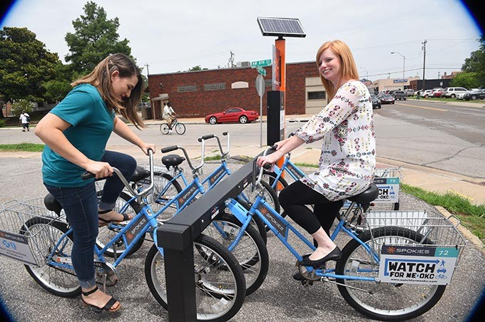 From left, Amanda Laija and Ashleigh Arnall try out the new Sokies bikes at the station in the Elemental Coffee parking lot at NW 8th and Hudson Avenue.  mh