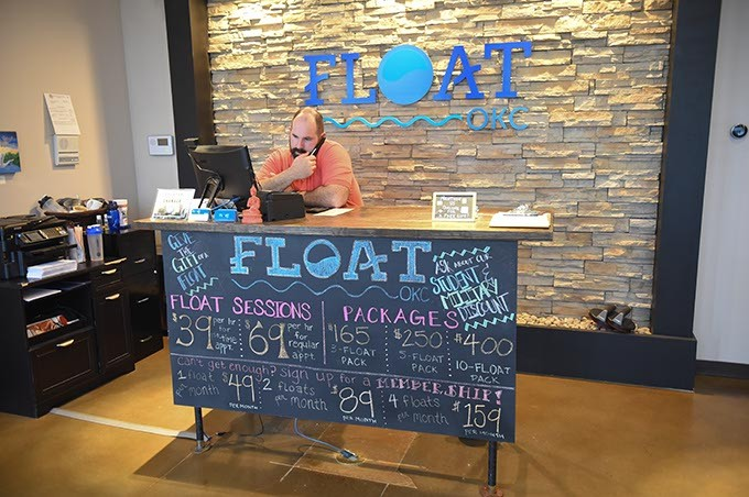 Matt Ligon, one of the owners of Float OKC, on the phone with customers at the front dest of the Edmond Business.  mh