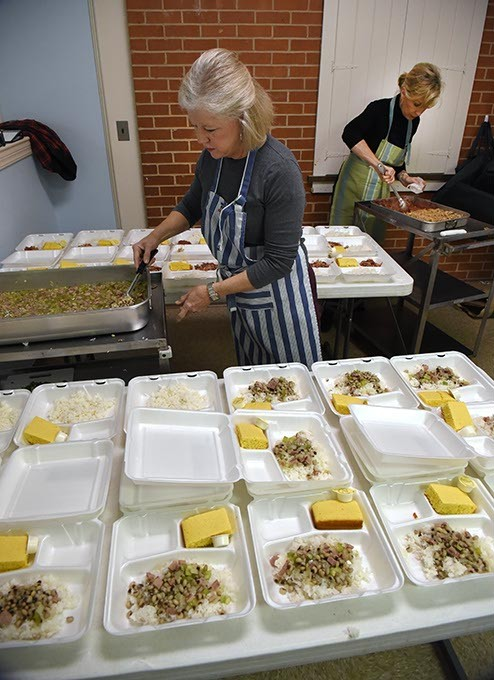 """From left, Barbara Hill and Alison Calhoon, volunteers with Westminster Presbyterian Church in Crown Heights, dole out portions of """"Hoppin Johns"""", cornbread, and cherry crisp dessert, for the  Mobile Meals program being delivered shortly after it's ready, to neady recepients on New Years Eve, 12-31-15, in OKC. - MARK HANCOCK"""