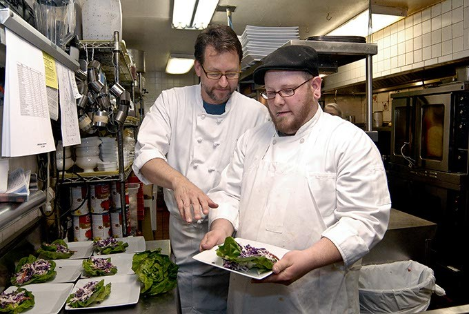 Chef Kurt Fleischfresser instructs apprentice Bandon Hall while making multiple salad plates for lunch, in the kitchen at The Coach House restaurant in Nichols Hills.  4-1-2008 Mark Hancock