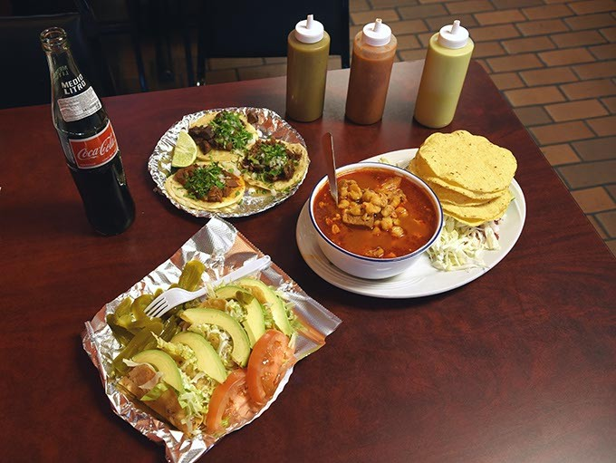 Up front are tacos de papa, with a bowl of pozole, and and a plate of three tacos in background, at Taqueria la Tropicana, and things go better with Coke, 12-21-15. - MARK HANCOCK