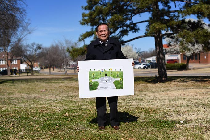 Vinh Nguyen poses for a photo with a picture of a American Community Vietnam Monument at Military Park in Oklahoma City. - GARETT FISBECK