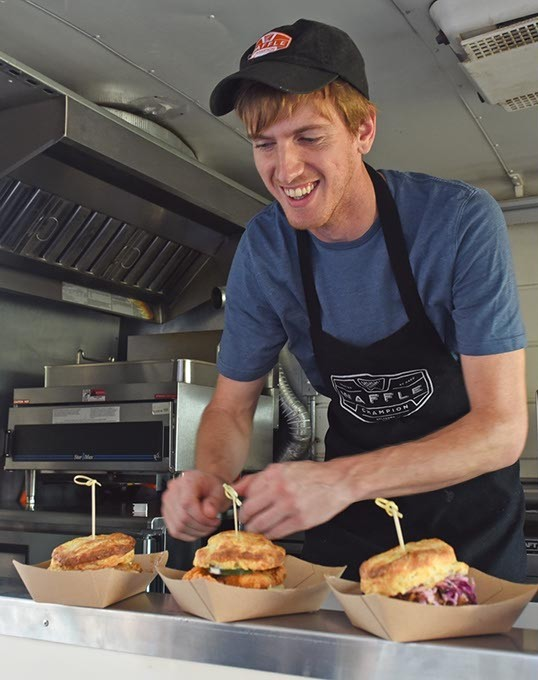 Peter O'Neal, Buttermilk Southern Sliders food truck manager, lines up their 4 sliders in the order window of the food truck.  mh