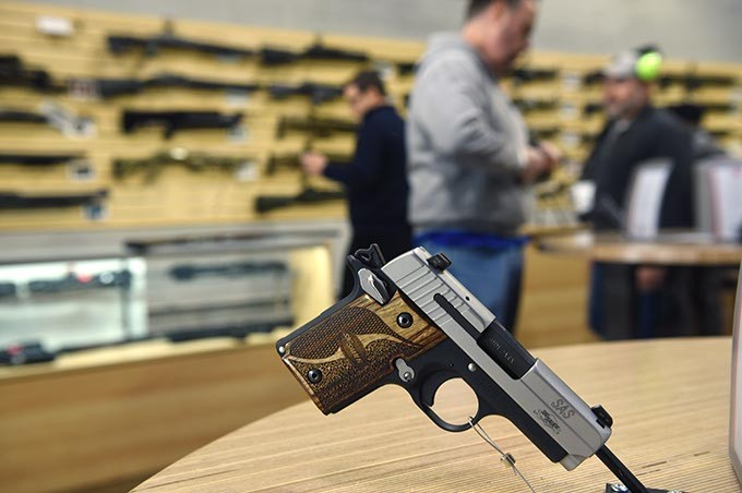 Shoppers can handle the pistols attached to convenient display tables at the new Wilshire Gun Range, photographed during grand opening, 11-14-14.  mh