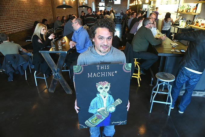 "Artist Anthony Pego with his sketch of Woody Guthrie as a cat holding a Marshall Brewing Company of Tulsa, IPA bear, at a special opening ""Getting Catty"" at Oak & Ore, 2-26-15.  mh"