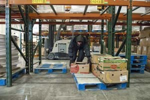 A warehouse worker grabs a box of bananas from a palet in the warehouse at Regional Food Bank of Oklahoma.  mh