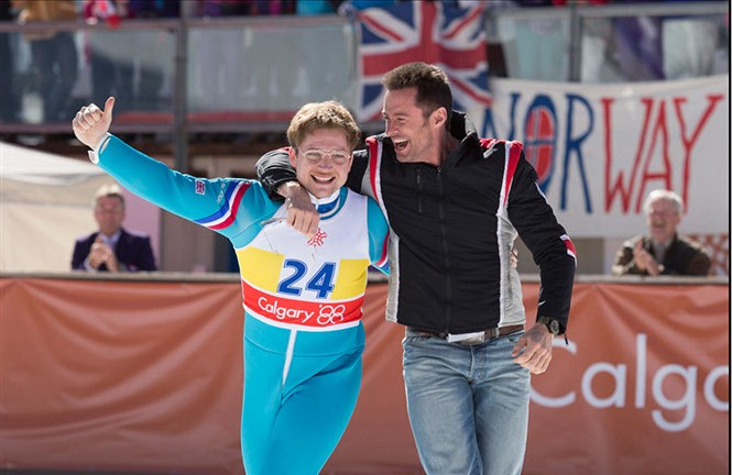 DF-01693_R - Eddie (Taron Egerton) and his coach Bronson Peary (Hugh Jackman) rejoice in Eddie's triumph. - PHOTO CREDIT: LARRY HORRICKS