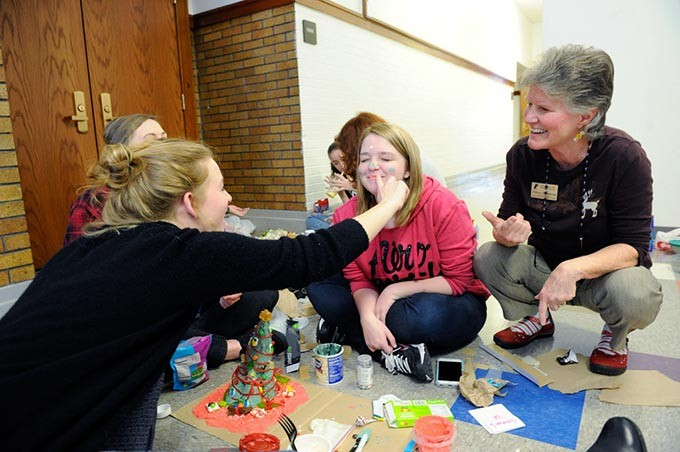 Lena Koehler puts frosting on Natalie Trujillo's face as Nancy Boudreau looks on at Classen SAS in Oklahoma City, Wednesday, Dec. 9, 2015. - GARETT FISBECK