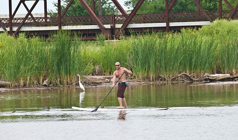 Eric Pappas mingles with wildlife as he demonstrates surf paddle board technique on the waterway connecting Stinchcomb Wildlife Refuge and Lake Overholser as it passed under the old Route 66 Bridge, Background. - MARK HANCOCK