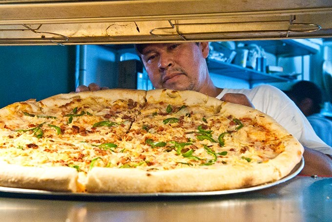 Jorge Resendiz places a large combo pizza in the pizza by the slice rack, at Empire Slice House.  mh