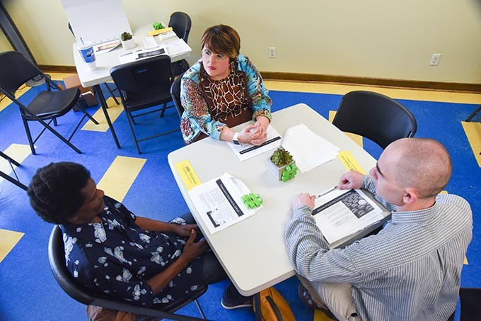 Augusta Cox speaks with Calvin Lewis, left, and Aaron Formhals during a Wellness Workshop at Lottie House, Wednesday, 7-5-15.  mh