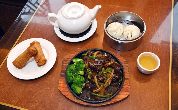 A spread of egg rolls, black pepper steak with broccoli, barbecue pork buns from the dim sum menu, and hot tea at Fung's Kitchen.  mh
