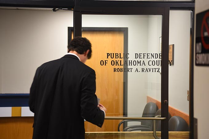 An attorney waits looks over his paperwork befere entering the Public Defender of Oklahoma County offices, 9-24-15. - MARK HANCOCK