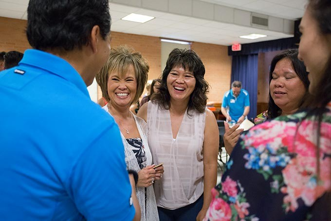 A small group of the 23 children, now adults, share a laugh. Gisela Huyssen and her husband Ulrich Huyssen adopted 23 Vietnamese children to American families at the end of the Vietnam war on Saturday, July 2, 2016 in Oklahoma City. - EMMY VERDIN