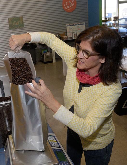Kari Starkey pours freshly roasted coffee into a bag at Leap Coffee Roasters in Oklahoma City, Monday, Jan. 16, 2016. - GARETT FISBECK