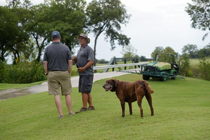 Chris Chesser, golf course director, and Derron Day, course superinendent, talk as Scout looks on at Firelake Golf Course in Shawnee, Monday, July 31, 2017. - GARETT FISBECK