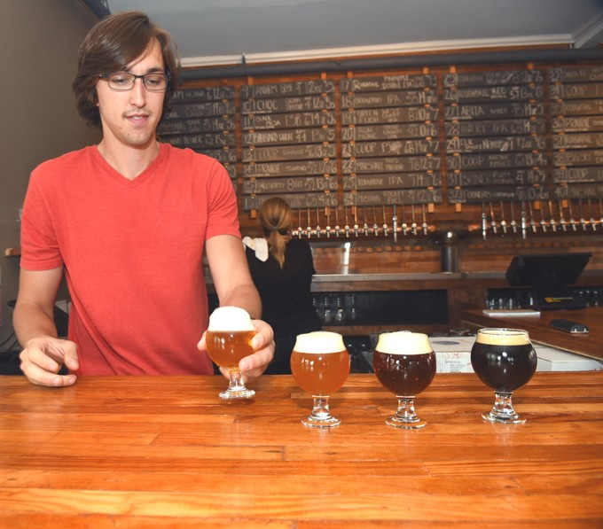 Bartender Chris Evans brings some tasters to the forfront prior to the start of a Roughtail Pint Night event, Thursday, 5-14-15.  mh