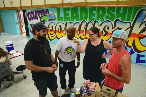 Left to right, Sean Vali, Warren Pete, school principal, Romy Owens, and Jason Pawley discuss murals on the cafeteria walls at F.D. Moon Elementary School, 1901 N.E. 13th Street in Oklahoma City, during the mural painting project, 7-14-16. - MARK HANCOCK
