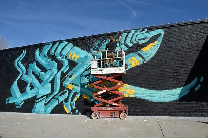 Sean Vali works on his mural in the Plaza District, Friday, Feb. 10, 2017. - GARETT FISBECK
