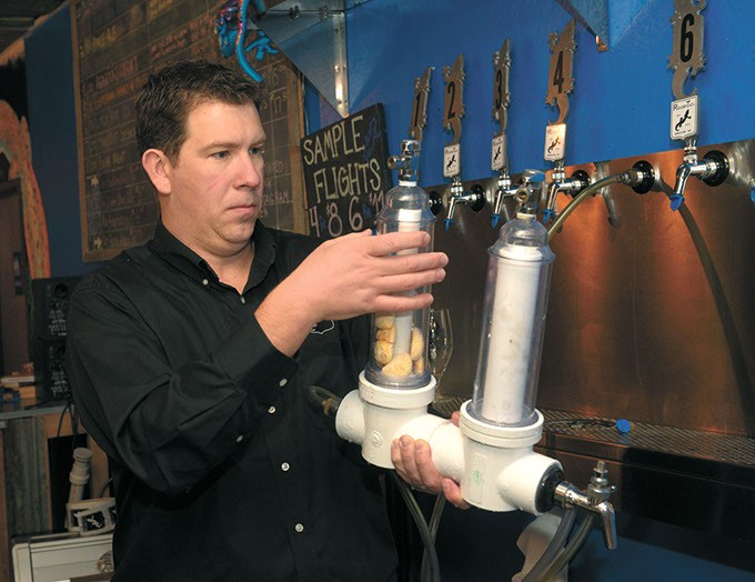 Blaine Stansel loads a randel beer infuser with savannah smiles at Roughtail Brewing Co. in Midwest City. (Garett Fisbeck)