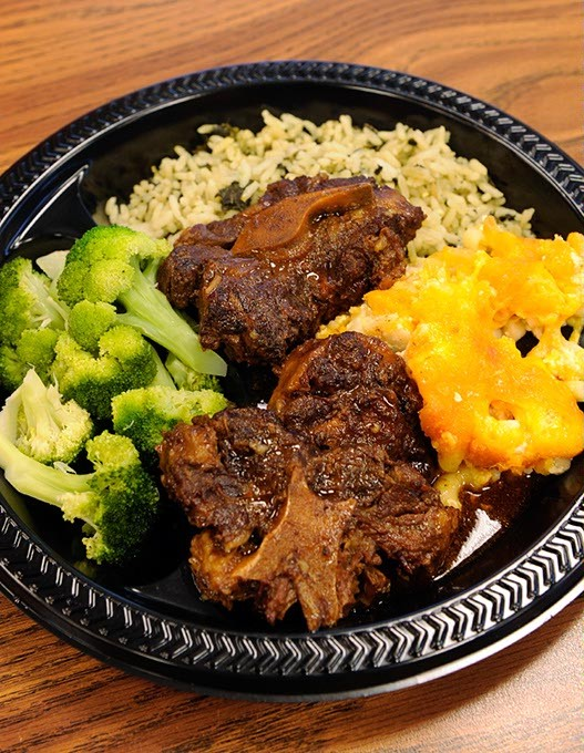 Oxtail, spinach rice, broccoli, macaroni and cheese, at Carican Flavors in Oklahoma City, Thursday, Dec. 18, 2015. - GARETT FISBECK