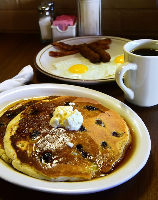 Breakfast with 2 eggs, bacon and Sasage, featuring a short stack of blueberry pancakes, at Woodbridge restaurant.  mh