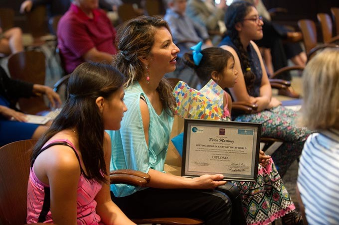 Perla Martinez sits with her family after receiving her diploma during a ReMerge graduation at the Oklahoma City Community Foundation, Thursday, June 30, 2016. - GARETT FISBECK
