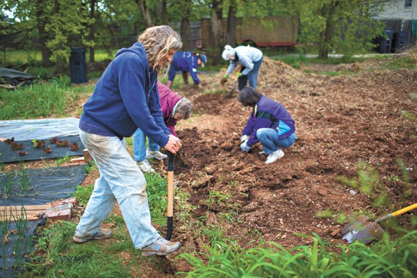 CommonWealth Urban Farms of OKC cofounder and farm manager Elia Woods and volunteers prepare soil for new planting beds. (Photo Bo Apitz / provided)