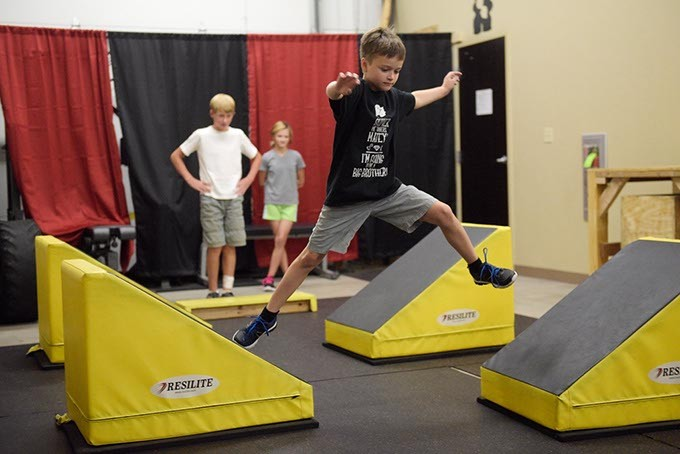 Gabe Conner, 9, runs a course as Jacob Wells, 11, and Cheyenne Conner, 11, look on during a class. (Photo Garett Fisbeck)